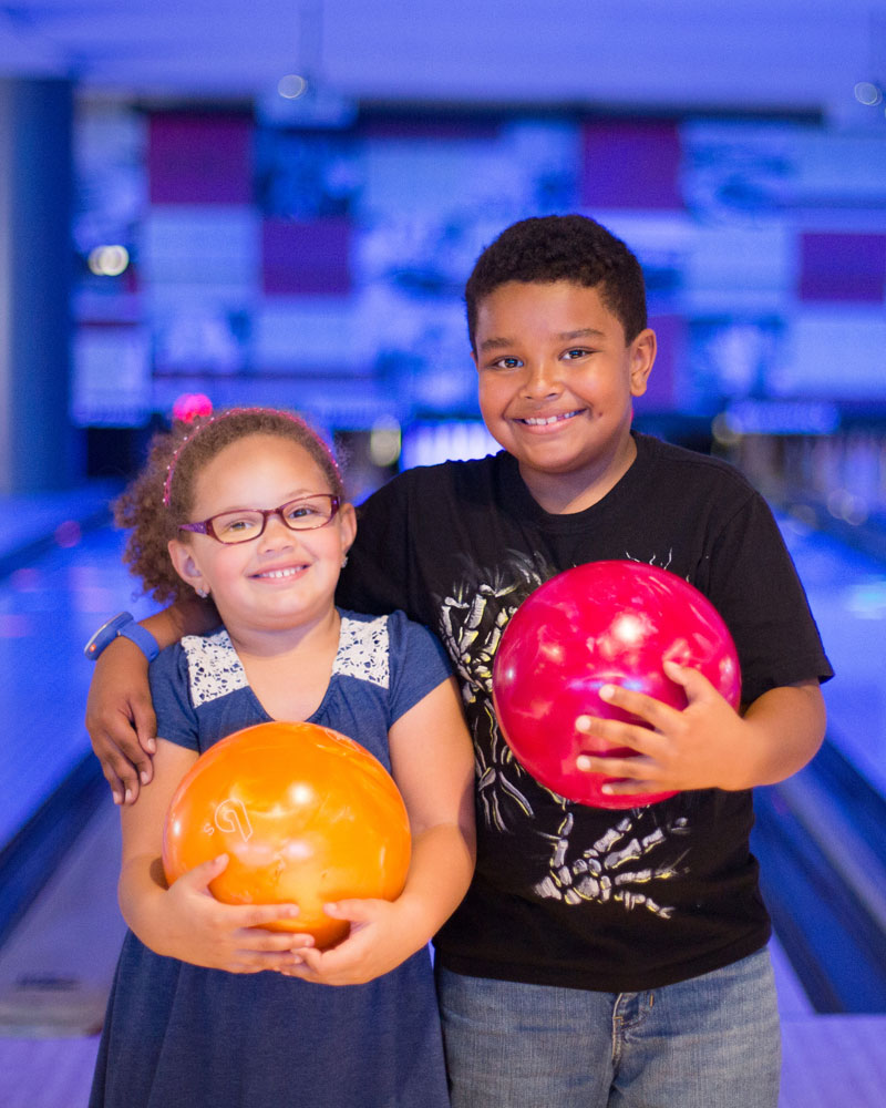 Two kids holding bowling balls and smiling